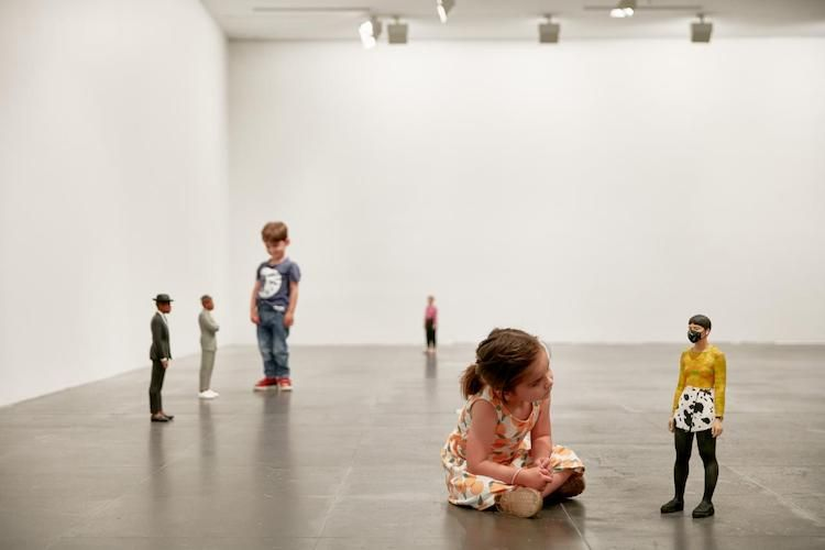 A little girl sits next to a Tomoaki Suzuki sculpture at the NGV Triennial 2020, little boy stands near sculpture in the background, activities for kids school holidays 2021 Melbourne